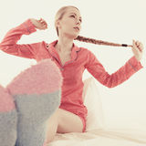 Woman in pajamas wearing furry warm socks Royalty Free Stock Images