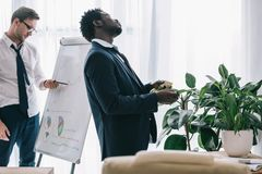 sleepy african american manager spraying plant with water at office while his colleague royalty free stock photos