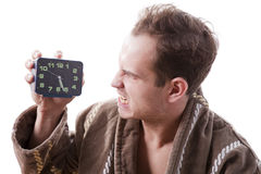 Sleepy angry man shouting in alarm clock in the early morning. Stock Images