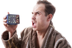 Sleepy angry man shouting in alarm clock in the early morning. Stock Image