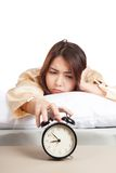 Sleepy Asian girl with alarm clock Stock Image