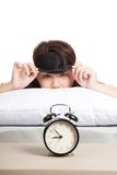 Sleepy Asian girl with eye mask and alarm clock Stock Photography