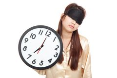 Sleepy Asian girl with eye mask hold a clock Stock Image