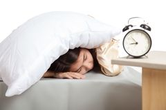 Sleepy Asian girl use pillow cover ears and alarm clock Royalty Free Stock Photography