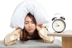 Sleepy Asian girl use pillow cover ears and alarm clock Stock Photography