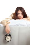 Sleepy Asian girl  wake up in bad mood with  alarm clock Royalty Free Stock Photography