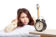 Sleepy Asian girl wake up hit alarm clock with hammer Stock Image