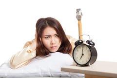 Sleepy Asian girl wake up hit alarm clock with hammer Stock Image