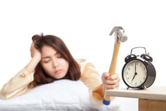 Sleepy Asian girl wake up hit alarm clock with hammer Stock Photography