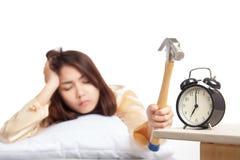 Sleepy Asian girl wake up hit alarm clock with hammer Stock Photography