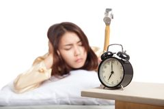 Sleepy Asian girl wake up hit alarm clock with hammer Royalty Free Stock Photography