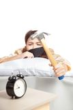 Sleepy Asian girl wake up hit alarm clock with hammer Stock Images