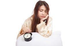 Sleepy Asian girl  wake up  with pillow and alarm clock Stock Photos