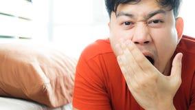 Sleepy Asian man on bed. stock image