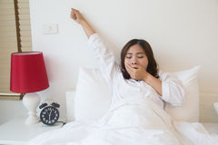 Sleepy asian woman yawning in bed Royalty Free Stock Image