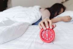 A sleepy Asian young woman holding a alarm. Clock.Soon to wake up for sleeping stock image