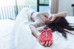 A sleepy Asian young woman holding a alarm. Clock.Soon to wake up for sleeping royalty free stock images