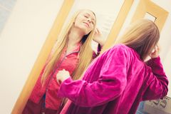 Woman looking at her reflection in mirror. Sleepy awaken woman standing in bathroom looking at her reflection in mirror after morning getting up yawning and stock photography
