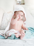 Sleepy baby boy covered in towel after bathing rubbing eyes Royalty Free Stock Image