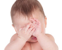 Sleepy baby covering the face with his hands Royalty Free Stock Images