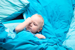 Sleepy baby in the crib with blue bedding. Rubs his eyes Stock Photos