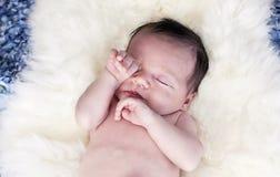 Sleepy baby. A sleepy newborn baby on a natural blanket Stock Photography