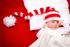 Sleepy baby on red blanket Stock Images