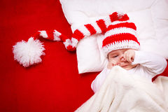 Sleepy baby on red blanket Royalty Free Stock Photography