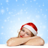 Sleepy beautiful young woman in santa claus hat laying on the ta. Ble on blue background with falling snowflakes Stock Photography