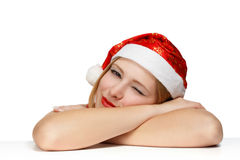 Sleepy beautiful young woman in santa claus hat laying on the ta. Ble isolated on white background Royalty Free Stock Photo