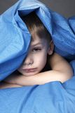 Sleepy boy. In blue bedclothes Stock Images