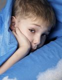 Sleepy boy. In blue bedclothes royalty free stock image