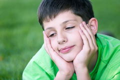 Sleepy boy in green on the green glade Royalty Free Stock Images