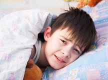 The sleepy boy has woken up in a bed. With a toy bear Stock Photo