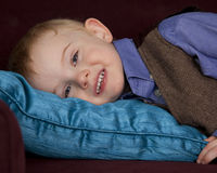 Sleepy boy on pillow. Young boy smile and lays on pillow stock images
