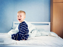 Sleepy boy sitting in bed Royalty Free Stock Image