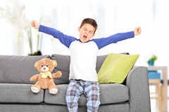 Sleepy boy yawning seated at a sofa indoors Stock Image