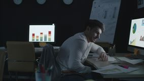 Fatigue business analyst sleeping on table front computer screen in night office. Sleepy business analyst stretching and yawning under financial data analysis in stock video footage