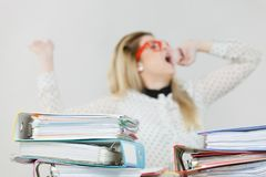 Sleepy business woman in office yawning. Sleepy business woman doing her work sitting working at desk full off documents in binders being bored or tired staying Stock Image