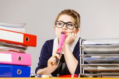 Sleepy business woman in office working. Sleepy business woman doing her work sitting working at desk full off documents in binders being bored or tired staying Royalty Free Stock Image