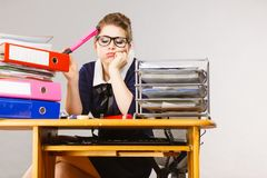 Sleepy business woman in office working. Sleepy business woman doing her work sitting working at desk full off documents in binders being bored or tired staying Royalty Free Stock Photo