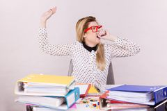Sleepy business woman in office working yawning. Sleepy business woman doing her work sitting working at desk full off documents in binders yawning being bored Royalty Free Stock Photo