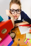 Sleepy business woman in office working. Sleepy business woman doing her work sitting working at desk full off documents in binders being bored or tired staying Royalty Free Stock Images