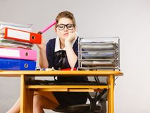 Sleepy business woman in office working. Sleepy business woman doing her work sitting working at desk full off documents in binders being bored or tired staying Royalty Free Stock Photography