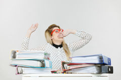 Sleepy business woman in office yawning. Sleepy business woman doing her work sitting working at desk full off documents in binders being bored or tired staying Royalty Free Stock Photography