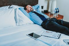 Tired businessman having short nap in his hotel room royalty free stock images