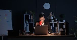 Sleepy businessman drinking coffee and working on laptop at night stock video footage