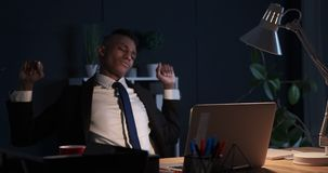 Sleepy businessman stretching and using laptop at night office stock video