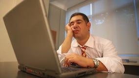 Sleepy businessman using laptop in office stock video