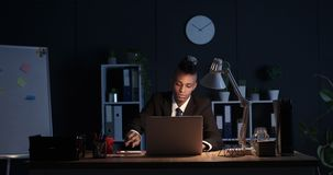 Sleepy businessman using laptop and taking notes in night office. Sleepy businessman working on laptop and taking notes at late night office stock footage